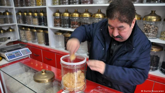 A man scoops something out of a sweet ja. Behind him are rows of glass jars