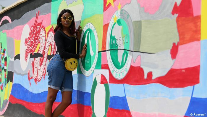 A young Nigerian woman against a graffiti wall