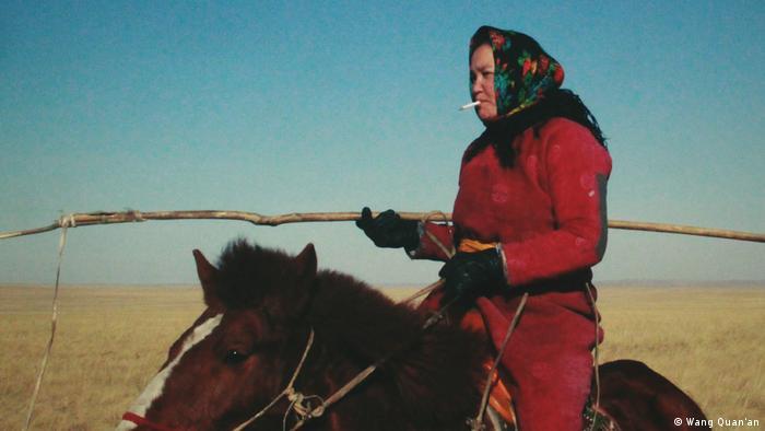 Filmszene aus Öndög zeigt eine Hirtin auf einem Pferd reitend (Wang Quan'an)