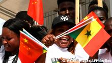 Senegalese hold Chinese and Senegalese flags upon the arrival of Chinese President Xi Jinping for a state visit on July 21, 2018 in Dakar. (Photo by SEYLLOU / AFP) (Photo credit should read SEYLLOU/AFP/Getty Images)