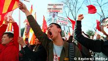 Chinese protesters yelling and carrying placards at the Madrid rally (Reuters/J. Medina)