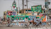 People ride bicycles past electoral posters and billboards in the Nigerian city of Mubi, Adamawa State, on February 15, 2019, on the eve of the country's presidential election. - Nigeria made final preparations on the eve of the presidential election, with candidates pitting continuity against reform in a battle between incumbent Muhammadu Buhari and his main rival Atiku Abubakar. (Photo by Luis TATO / AFP) (Photo credit should read LUIS TATO/AFP/Getty Images)