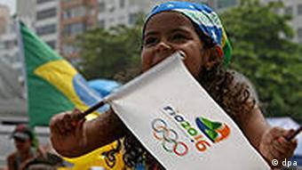 Ein kleines Mädchen winkt mit der Olympia-Flagge (Foto: AP)