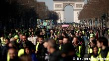 Protesters wearing yellow vests walk down the Champs Elysees from the Arc de Triomphe as they take part in a demonstration (Reuters/B. Tessier)