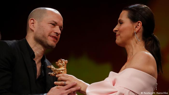Foto do diretor Nadav Lapid recebendo Urso de Ouro da atriz Juliette Binoche, presidente do júri da Berlinale
