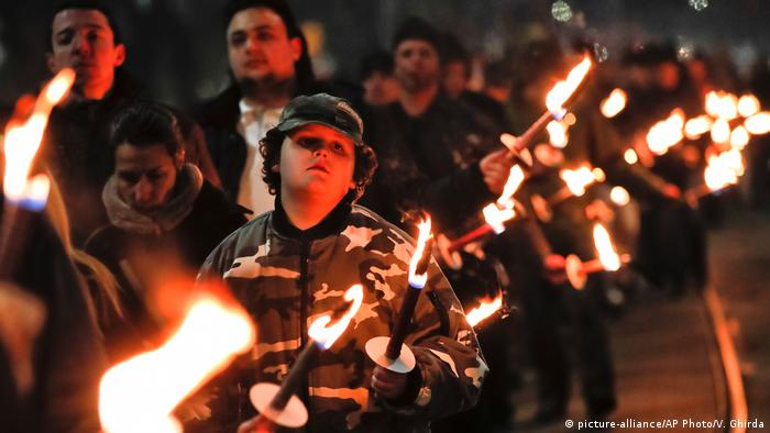 Young protester in a military styile jacket holds a torch