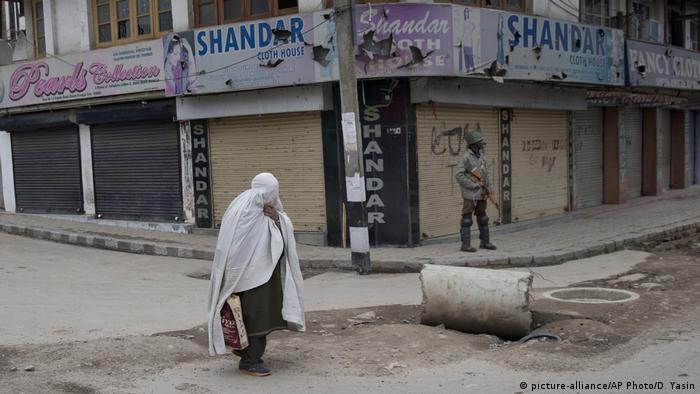 A Kashmiri burqa clad woman walks past an Indian paramilitary soldier