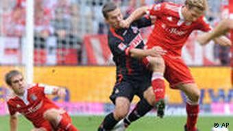 Münchens Ottl (r.) und Kölns Podolski (m.) im Zweikampf. (Foto: AP Photo/Christof Stache)