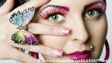 Junge Frau mit künstlichen WImpern und einem Schmetterling als Ring