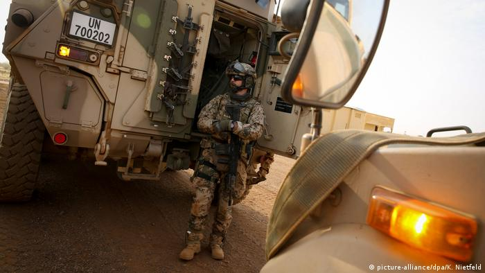 An armed German soldier secures a tank in Mali