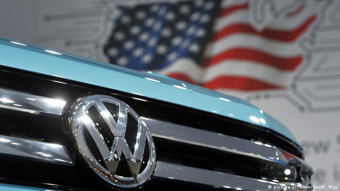 A VW emblem on a car with a red, white and blue US flag in the background (picture-alliance/dpa/F. May)
