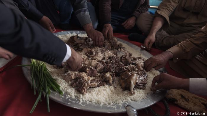 A group of men eating lamb and rice (DW/B. Gerdziunas)