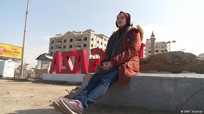 Hala Shoman, a dentist sitting on a slab of rock
