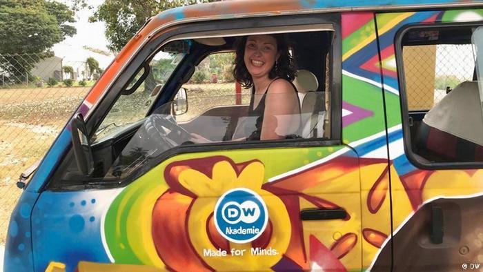 Die Freiwillige Sophia in einem bunt bemalten Kleinbus bei ihrer Arbeit in Ghana