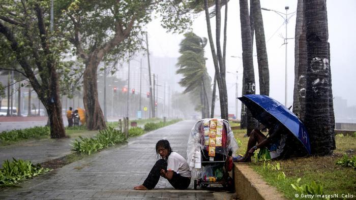 Vendedor de rua treme na chuva enquanto chuvas do tuão Yutu atingem a baía de Manila em outubro de 2018.