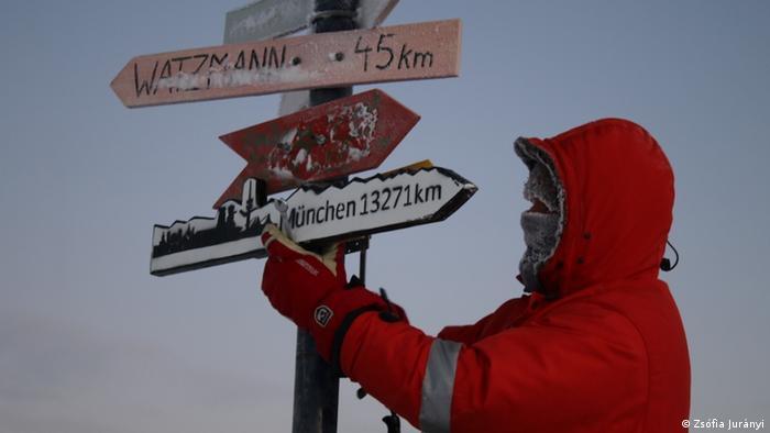 Tim Heitland vor Wegweisern in der Antarktis