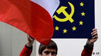 An anti-Lisbon treaty protester holds up a Czech flag and a flag with the EU stars with a hammer and sickle in the middle