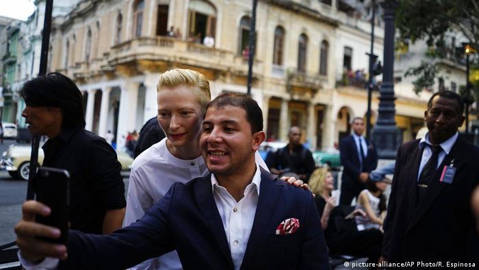 Tilda Swinton taking a selfie with a a man in a suit