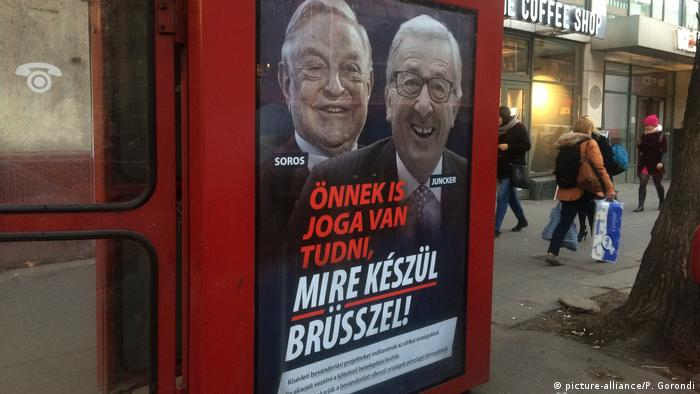 """A phone box displays a billboards showing Hungarian-American financier George Soros and European Commission President Jean-Claude Juncker above the caption """"You have a right to know what Brussels is preparing to do!, on Vaci Avenue in Budapest, Hungary, Tuesday, Feb. 19, 2019"""