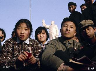 Chinese children sit holding their Little Red Books of Chairman Mao's quotations in Shanghai, date unknown. In the background is a statue of Mao. (AP Photo)
