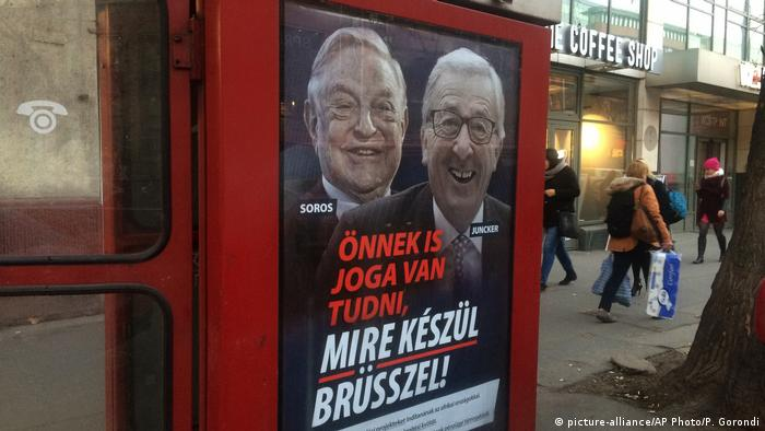 "A phone box displays a billboards showing Hungarian-American financier George Soros and EU Commission President Jean-Claude Juncker above the caption ""You have a right to know what Brussels is preparing to do!, on Vaci Avenue in Budapest, Hungary, Tuesday, Feb. 19, 2019 (picture-alliance/AP Photo/P. Gorondi)"