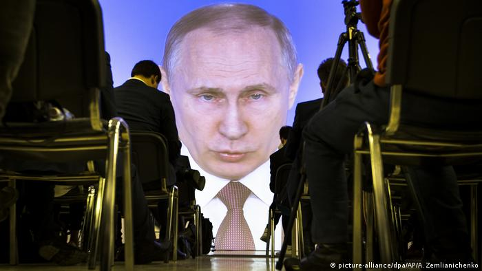 Putin's head floats on a screen above the audience listening to him speak