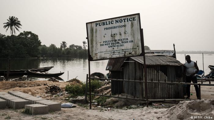 An order signboard in front of a polluted river with the message can read Polluted water - Do not drink, or swim here at the River Bodo in Niger Delta region in Nigeria