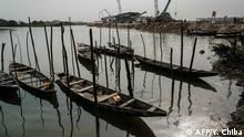 Fishing boats are seen next to a bridge construction site on the River Bodo, which was damaged by the devastating oil spills from the pipeline about 10 years ago in Bodo village of Ogoniland, which is part of the Niger Delta region, Nigeria, on Feburuary 19, 2019. - Two oil spills caused by corroded pipelines of Anglo-Dutch oil giant Shell between 2008 and 2009 destroyed the ecosystem of the creeks in the Niger Delta. Shell has paid compensation to the communities and promised clean-up operation but oil remains along the river bank. (Photo by Yasuyoshi CHIBA / AFP)