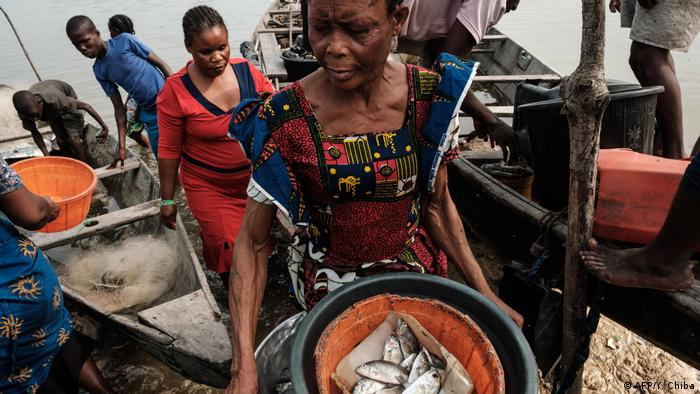 A woman carrying fish from a dock in Nigeria