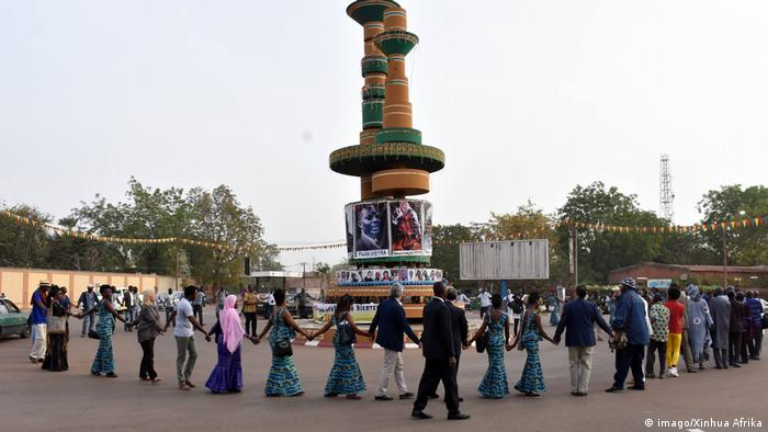 People dancing aroud a statue of two monumental film reels (imago/Xinhua Afrika)