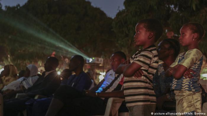Children standing and aduls sititng watching a movie (picture-alliance/dpa/EPA/N. Bothma)