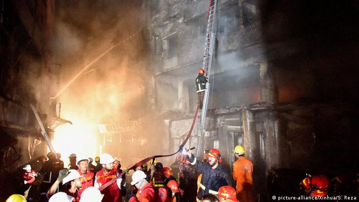 Firefighters climb a ladder leading against a charred building