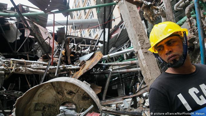 A rescue worker looks for survivors at the site of the Gazipur factory collapse