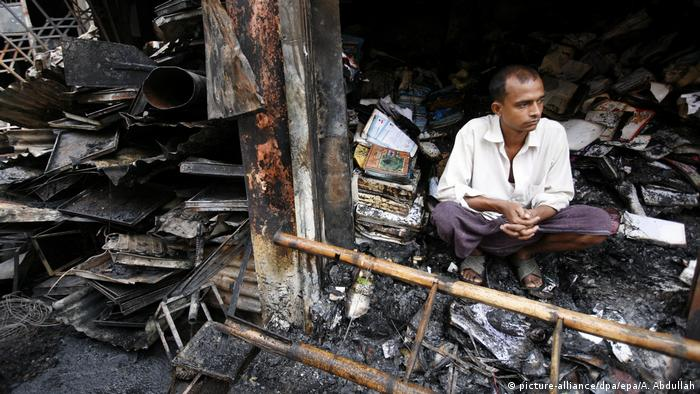 A man sits in front of his burnt-out shop