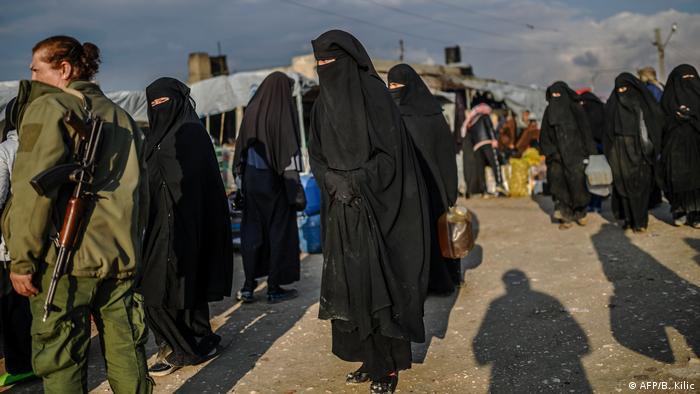 Militar e diversas mulheres de burca em campo de refugiados