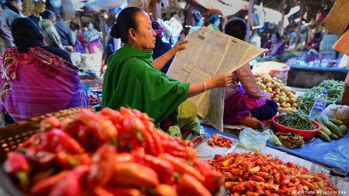 A Manipuri woman reads a newspaper at the Ima market