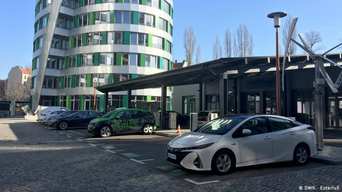 View of a parking lot with various electric cars being charged