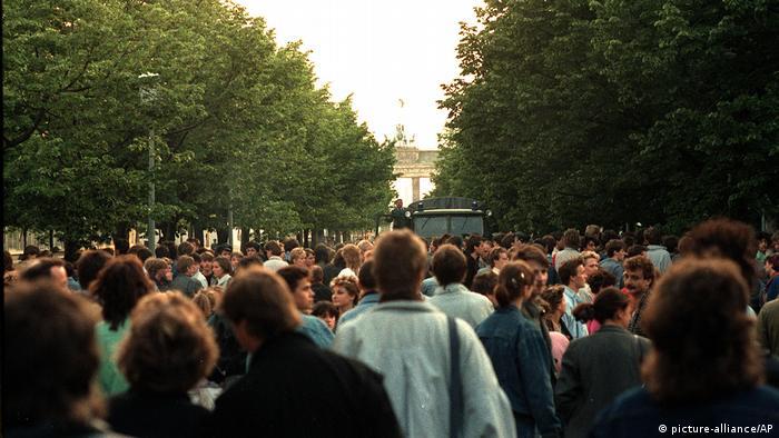 Menschenmasse, in der Mitte Polizeiauto, im Hintergrund das Brandenburger Tor (Foto: picture-alliance)