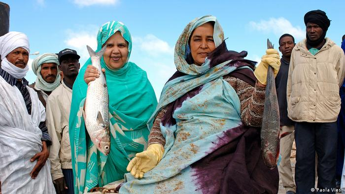 Two women hold up dead fish, while a group of men look on