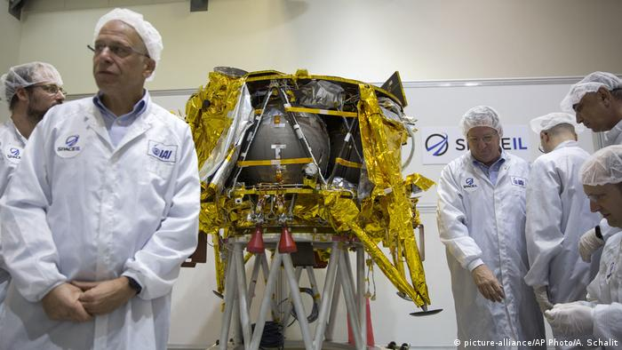 Technicians stand with the Berescheet lunar module, a robotic moon lander, that will leave a time capsule there