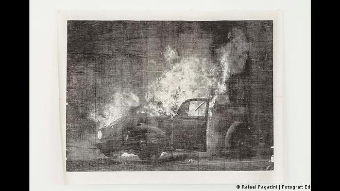 Man sieht einen brennenden VW-Käfer