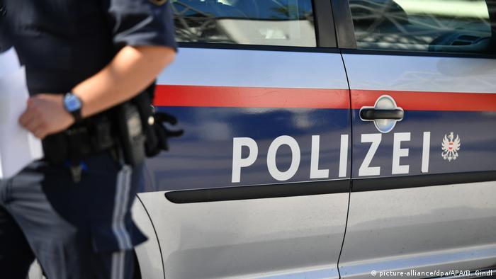 Австрийский полицейский рядом со служебным автомобилем