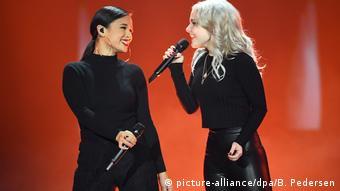 ESC-Vorentscheid Unser Lied für Israel: Das Duo S!sters steht beim Vorentscheid für den Eurovision Song Contest Unser Lied für Israel auf der Bühne, laurita links, Carlotta rechts, sie gucken und lächeln sich an vor rotem Hintergrund