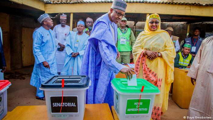 Nigerian President Muhammadu Buhari places his ballot into a box during the 2019 election. He is surrounded by his wife, his advisers and election officials
