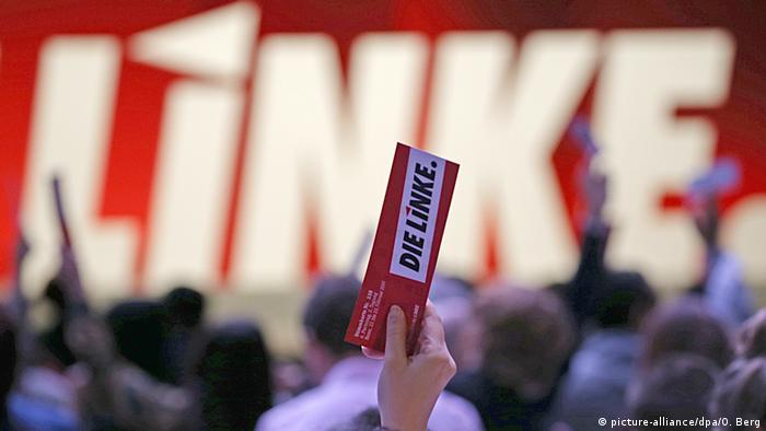 A delegate at the Left Party convention in Bonn holds up a slip of paper (picture-alliance/dpa/O. Berg)
