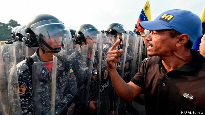 Один из демонстрантов спорит с венесуэльскими военными