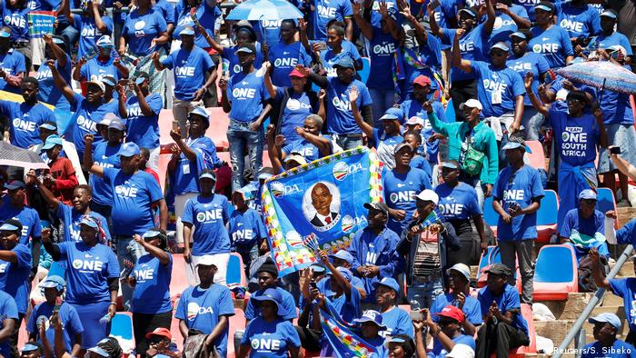 Democratic Alliance supporters stand and wave flags (Reuters/S. Sibeko)