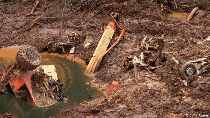 The remnants of a tractor and other debris swamped by mud after the Brumadinho dam disaster