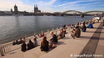 Menschen sitzen in der Sonne in Köln am Rheinboulevard