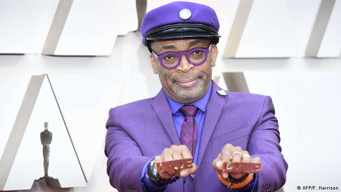 Spike Lee showing his knuckle rings 'Love' and 'Hate' and wearing a purple hat, glasses and a suit.